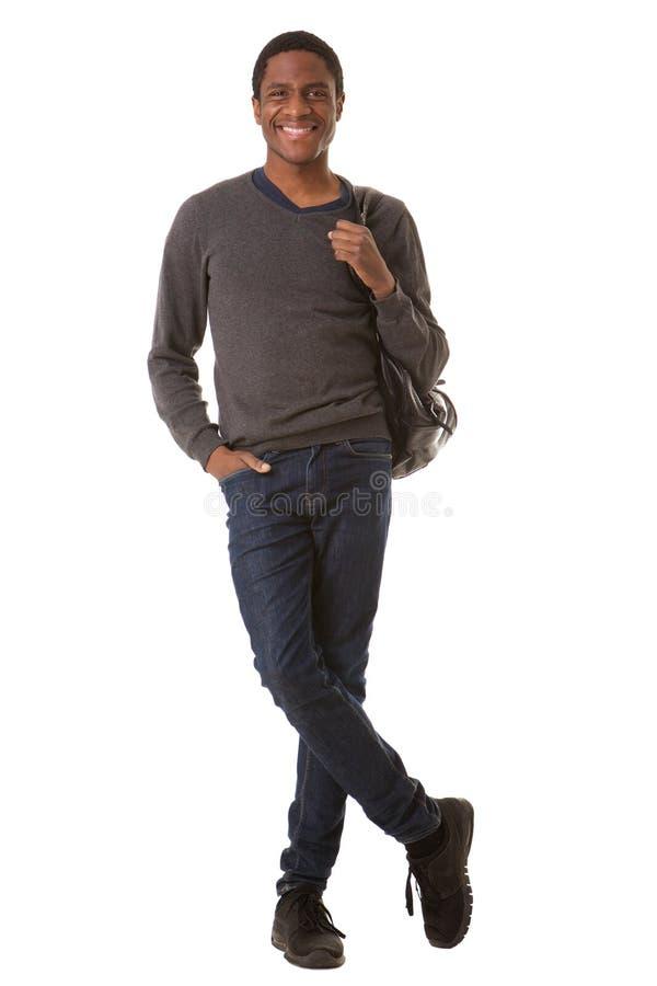 Jeune homme de couleur beau intégral souriant avec le sac sur le fond blanc d'isolement image stock