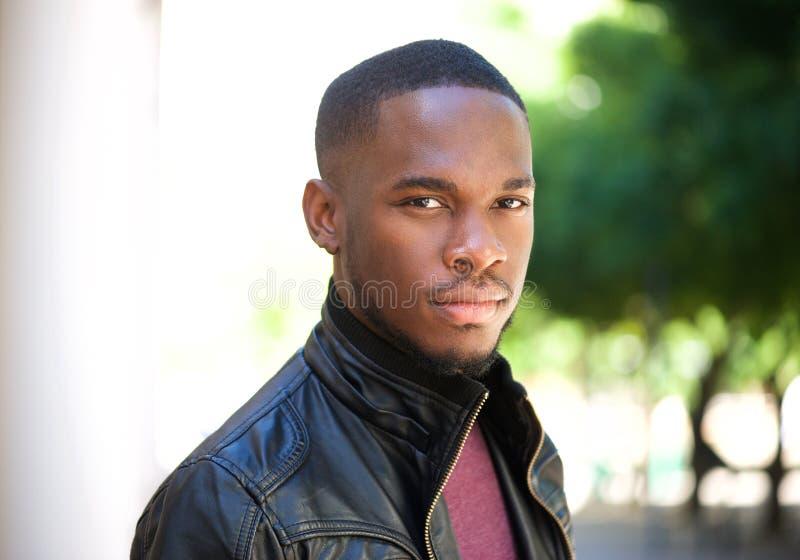 Jeune homme de couleur beau posant dehors image stock