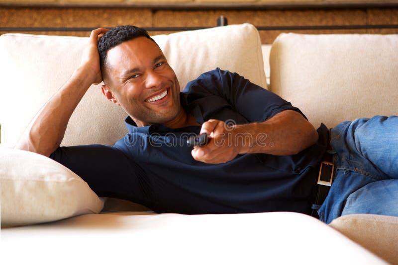 Jeune homme de couleur décontracté regardant la TV à la maison photos stock
