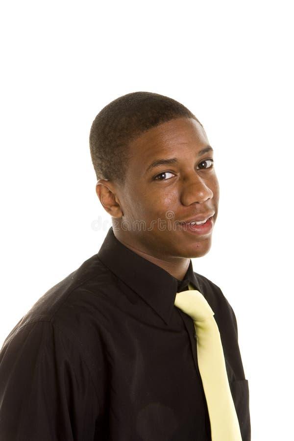 Jeune homme de couleur dans la chemise noire et la relation étroite jaune image stock