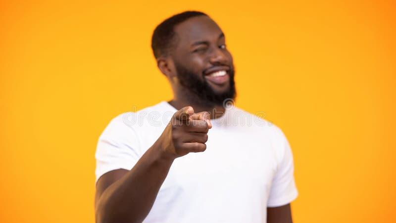 Jeune homme de couleur dirigeant le doigt sur la caméra et souriant sur le fond jaune photos libres de droits