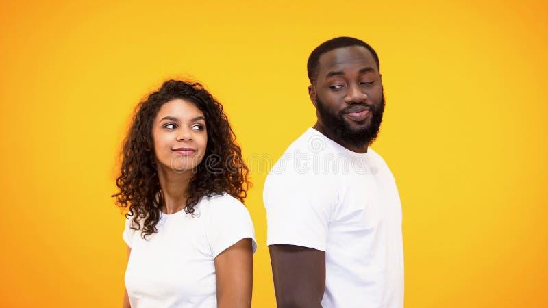 Jeune homme de couleur et femme se regardant se tenant de nouveau au dos, affection photo stock