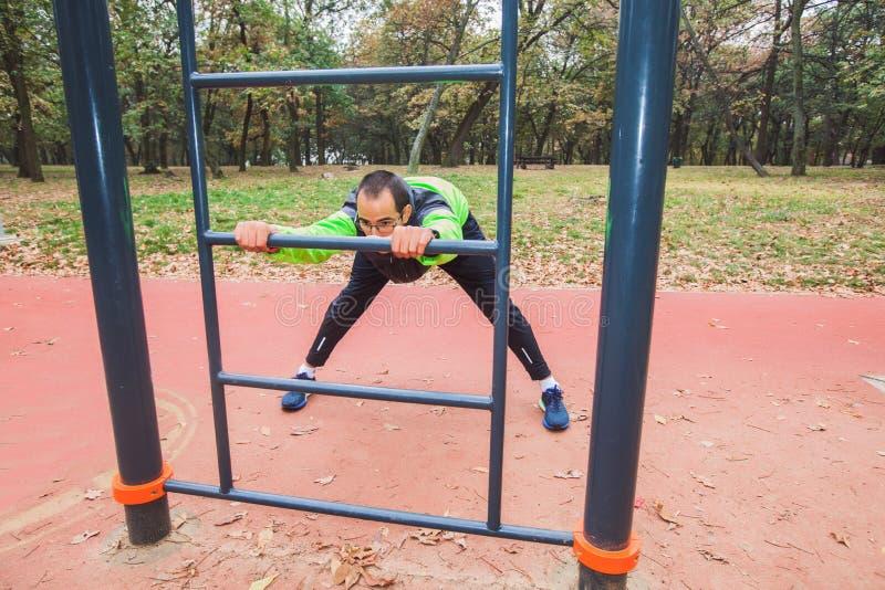 Jeune homme de forme physique faisant étirant la séance d'entraînement extérieure d'exercice photographie stock