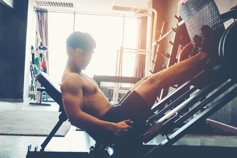 Jeune homme de forme physique s'exerçant utilisant la machine à ramer dans le gymnase photographie stock libre de droits