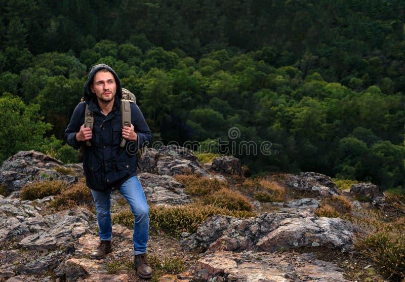 Jeune homme de hippie avec le sac à dos appréciant la montagne Voyageur de touristes sur la moquerie de forêt de vue de fond vers image stock