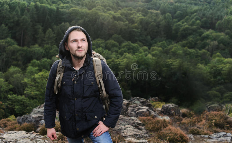 Jeune homme de hippie avec le sac à dos appréciant la montagne Voyageur de touristes sur la moquerie de forêt de vue de fond vers photographie stock