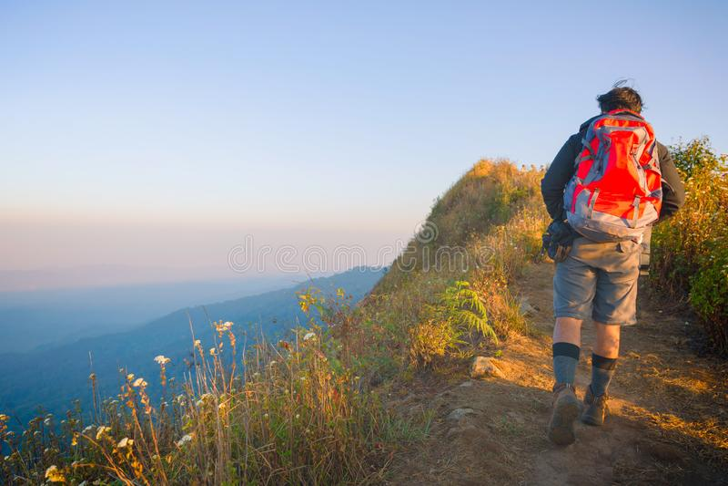 Jeune homme de hippie avec le sac ? dos appr?ciant le coucher du soleil sur la montagne maximale image libre de droits