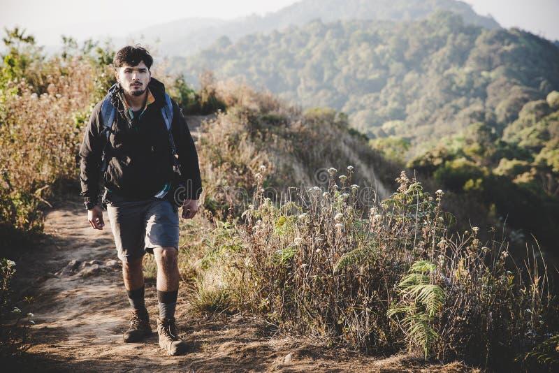 Jeune homme de hippie avec le sac ? dos appr?ciant le coucher du soleil sur la montagne maximale image stock
