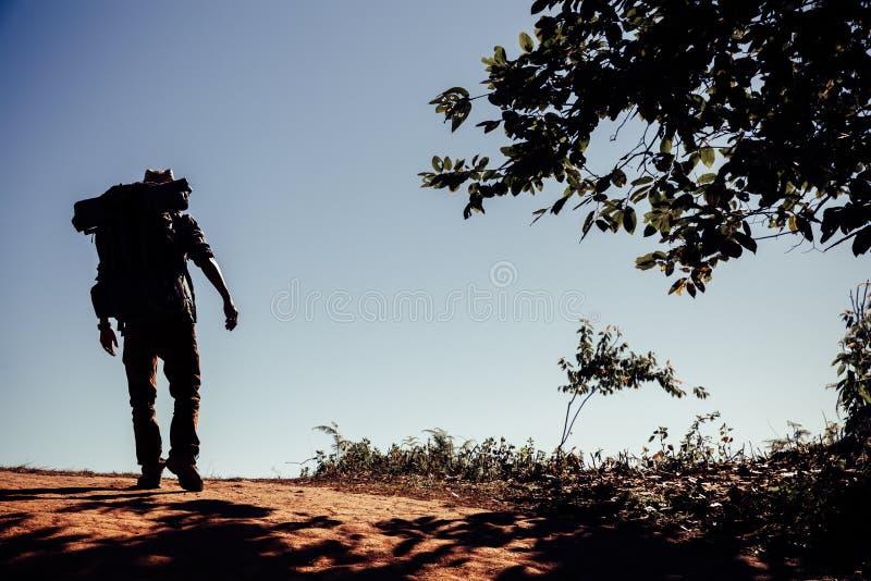 Jeune homme de hippie avec le sac ? dos appr?ciant le coucher du soleil sur la montagne maximale photos stock