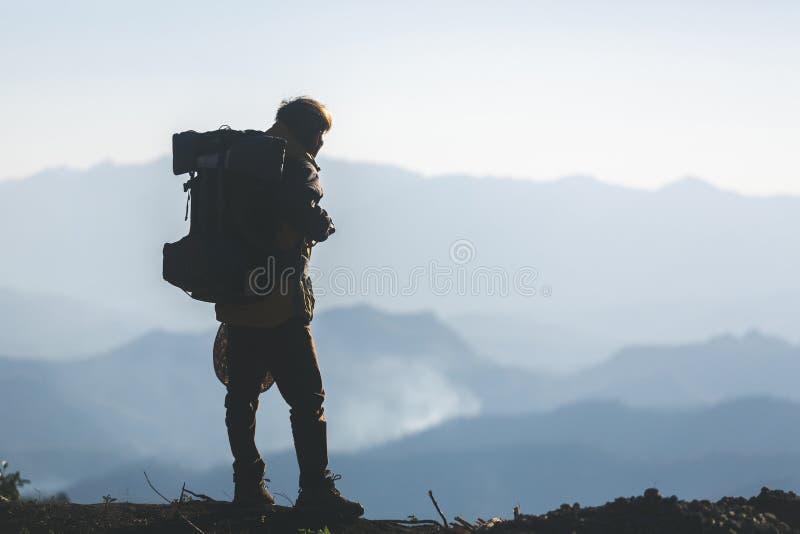 Jeune homme de hippie avec le sac ? dos appr?ciant le coucher du soleil sur la montagne maximale photo stock