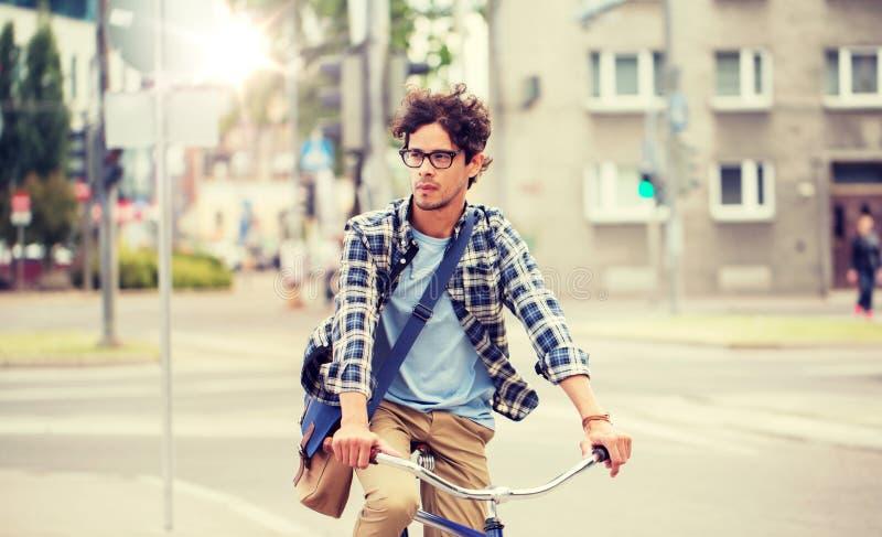 Jeune homme de hippie avec le v?lo fixe de monte de vitesse de sac images stock
