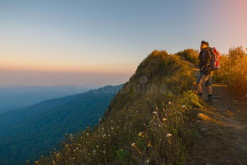 Jeune homme de hippie avec un sac à dos, appréciant le coucher du soleil sur le sommet photo libre de droits
