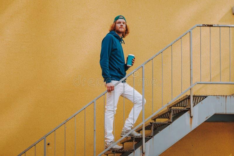 Jeune homme de hippie marchant sur des escaliers avec du caf? photos libres de droits