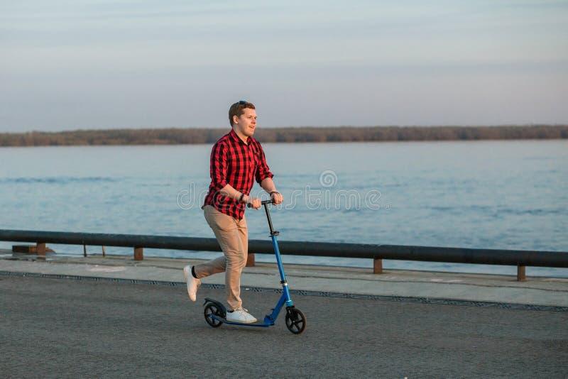 Jeune homme de hippie, montant sur un scooter de coup-de-pied après travail sur le coucher du soleil Concept de transport mobile  photographie stock libre de droits