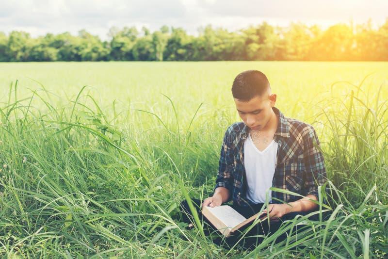 Jeune homme de hippie s'asseyant sur le livre de lecture de prairie avec la nature image stock