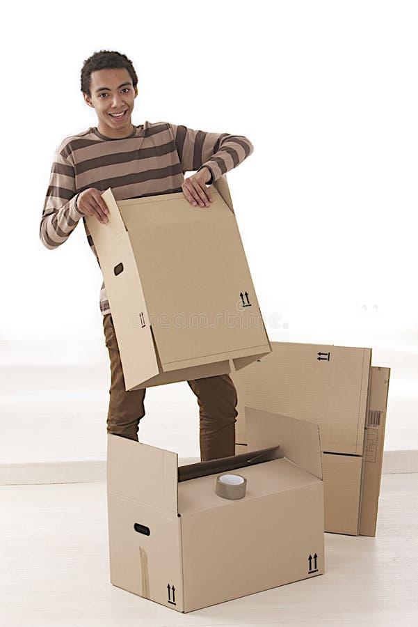 Jeune homme de mulâtre emballant vers le haut des boîtes photos stock