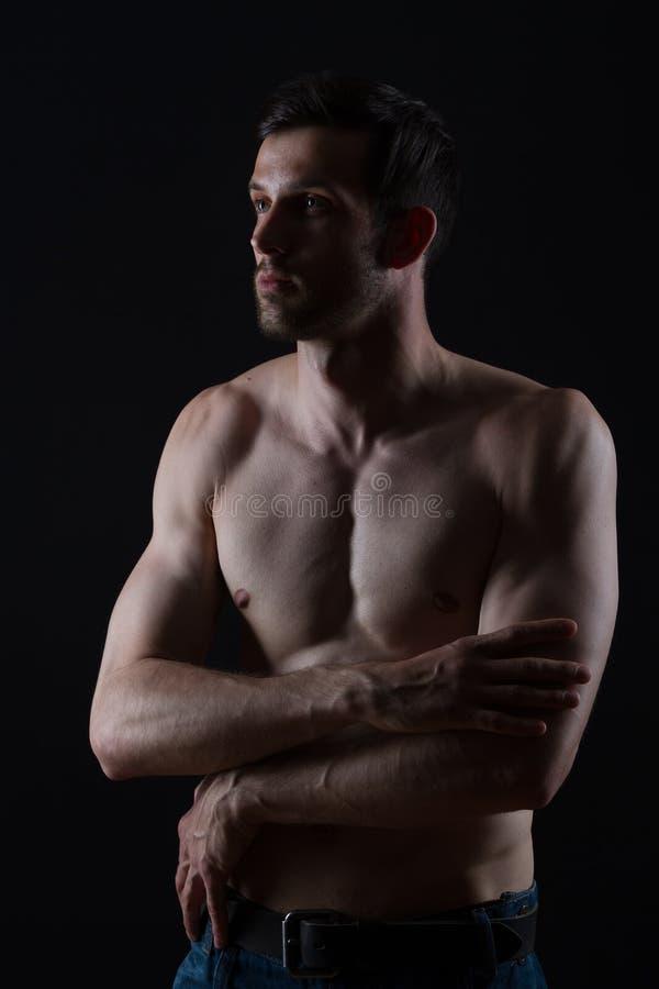 Jeune homme de muscles détendant sur le fond noir image libre de droits