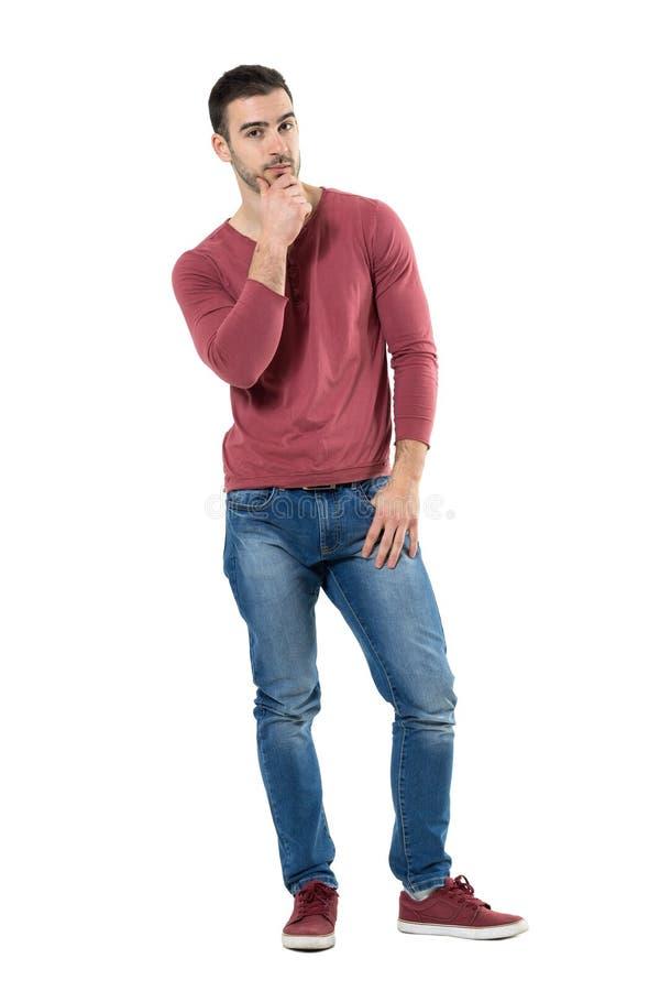 Jeune homme de pensée de style occasionnel avec des mains sur le menton regardant l'appareil-photo photographie stock libre de droits