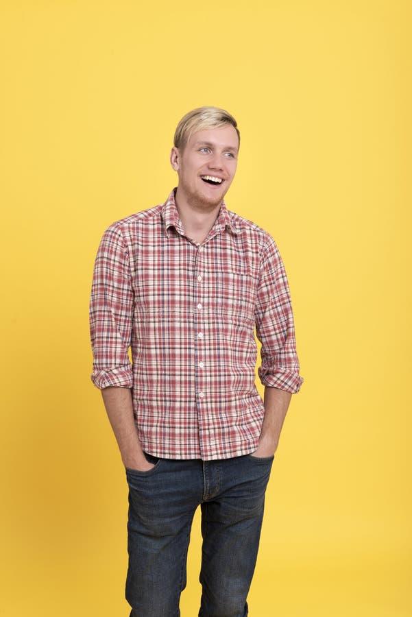 Jeune homme de rire portant la position rouge de chemise de plaid d'isolement au-dessus du fond jaune images libres de droits