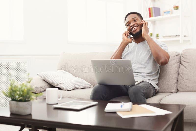 Jeune homme de sourire à la maison avec l'ordinateur portable et le mobile images stock