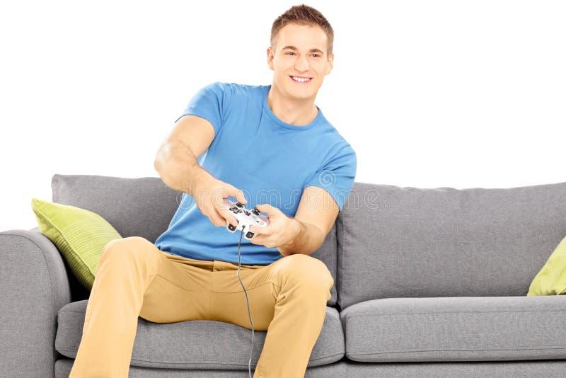 Jeune homme de sourire assis sur un divan jouant le jeu vidéo photographie stock