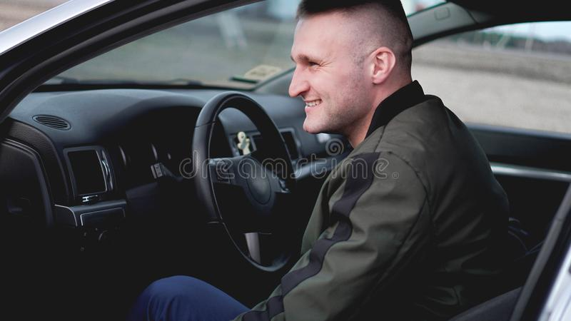 Jeune homme de sourire attirant dans une voiture image stock