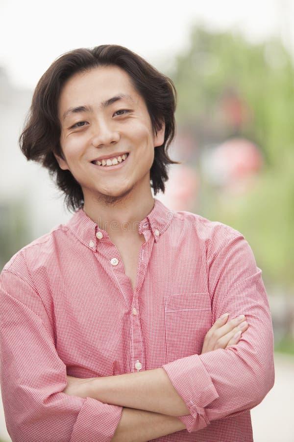 Jeune homme de sourire avec de longs cheveux dans Nanluoguxiang, Pékin, Chine image stock