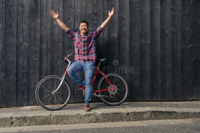 Jeune homme de sourire avec un vélo soulevant ses bras vers le ciel image libre de droits