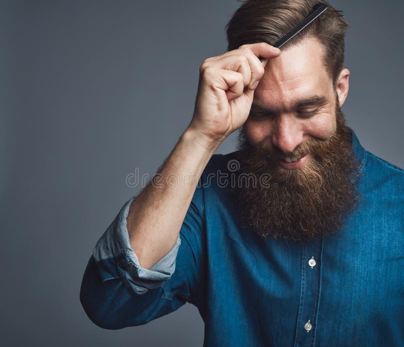Jeune homme de sourire avec une barbe dénommant ses cheveux image stock