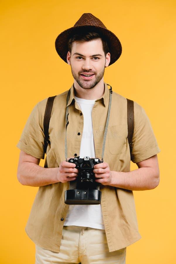 Jeune homme de sourire beau dans le chapeau tenant l'appareil-photo photos stock
