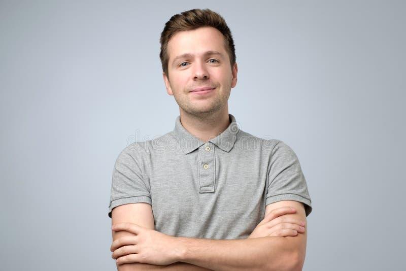 Jeune homme de sourire bel dans le T-shirt se tenant avec les mains croisées photographie stock