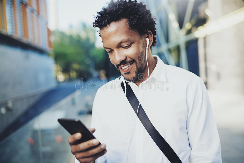 Jeune homme de sourire d'Afro-américain dans l'écouteur marchant à la ville ensoleillée et appréciant pour écouter la musique sur images stock
