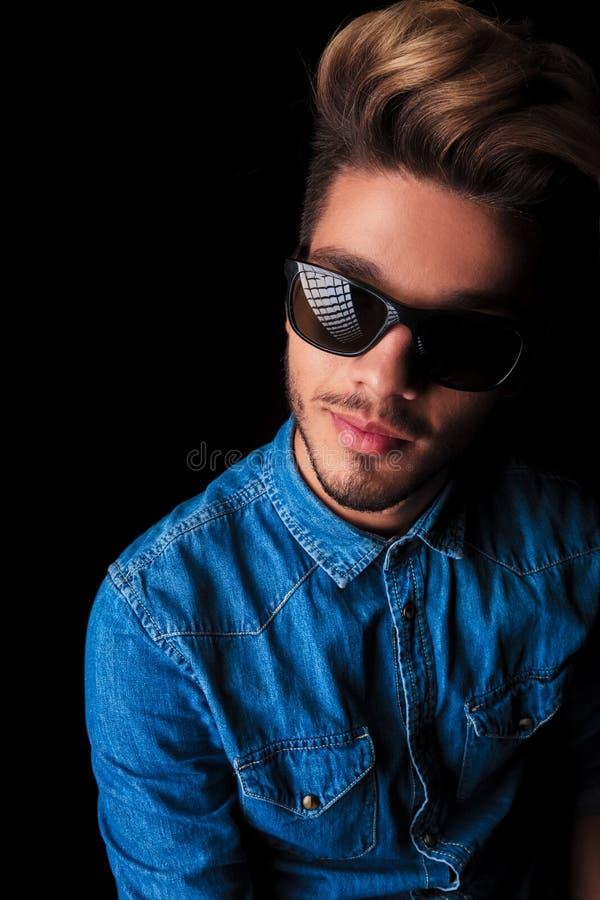Jeune homme de sourire dans des lunettes de soleil de port de chemise de denim photos libres de droits