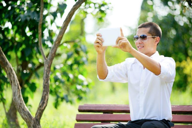 Jeune homme de sourire dans des lunettes de soleil prenant le selfie par le comprimé photographie stock libre de droits