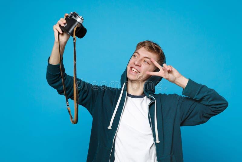 Jeune homme de sourire dans des vêtements sport faisant le selfie tiré sur la rétro caméra de photo de cru, montrant le signe vic photo libre de droits