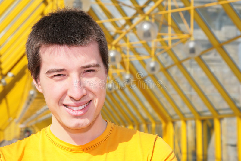 Jeune homme de sourire dans la chemise jaune photographie stock