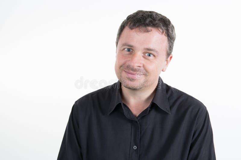 Jeune homme de sourire dans la chemise noire sur le blanc photographie stock