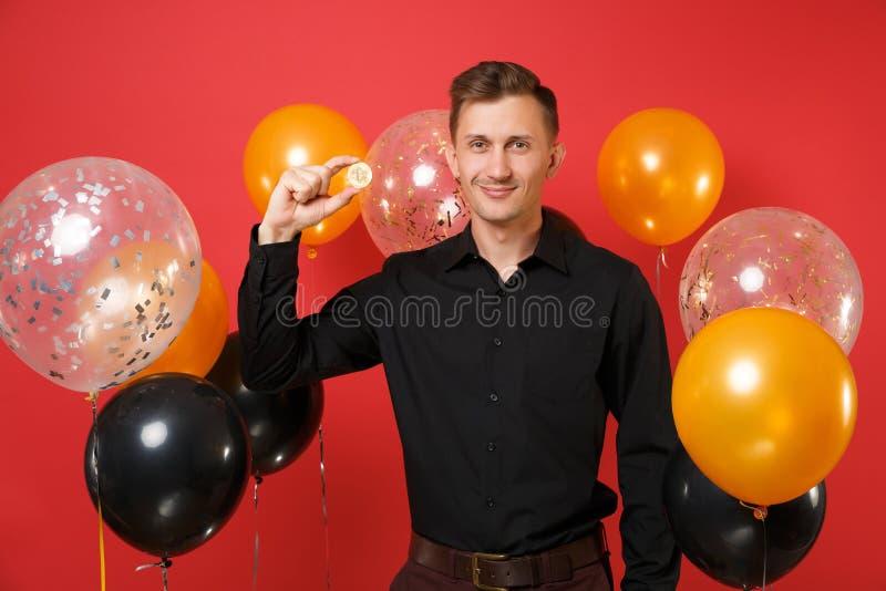 Jeune homme de sourire dans le bitcoin classique noir de prise de chemise, pièce de monnaie en métal de couleur d'or, future devi images stock