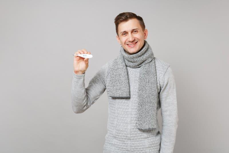 Jeune homme de sourire dans le chandail gris, thermomètre de participation d'écharpe sur le fond gris de mur, portrait de studio  images libres de droits