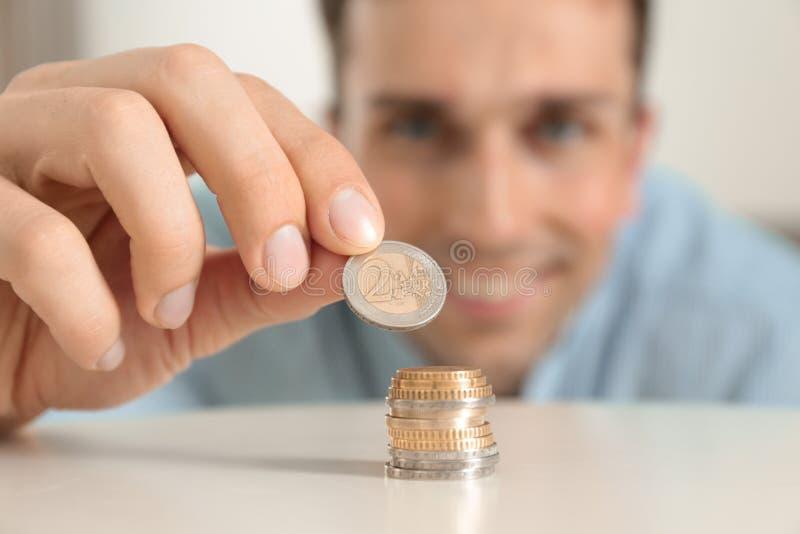 Jeune homme de sourire empilant des pièces de monnaie à la table photo libre de droits