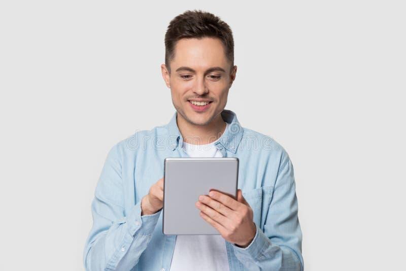 Jeune homme de sourire employant la position moderne de comprimé sur le fond gris images stock
