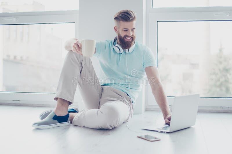 Jeune homme de sourire gai heureux s'asseyant sur le plancher buvant c images stock