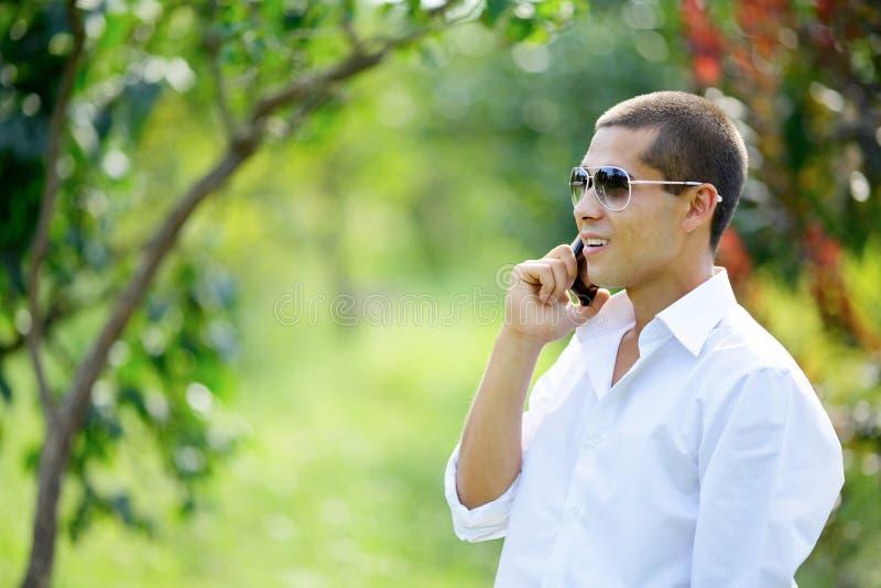 Jeune homme de sourire parlant à un téléphone portable images libres de droits