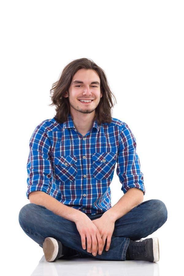 Jeune homme de sourire s'asseyant sur le plancher avec des jambes croisées. photos stock