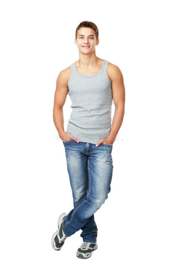 Jeune homme de sourire se tenant avec des mains dans des poches photos stock