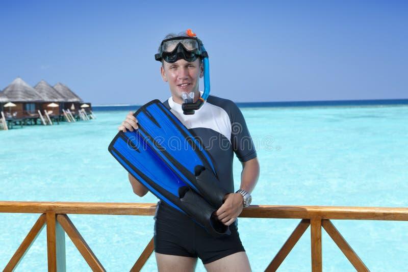 Jeune homme de sports avec les nageoires, le masque et le tube près de la mer maldives images libres de droits