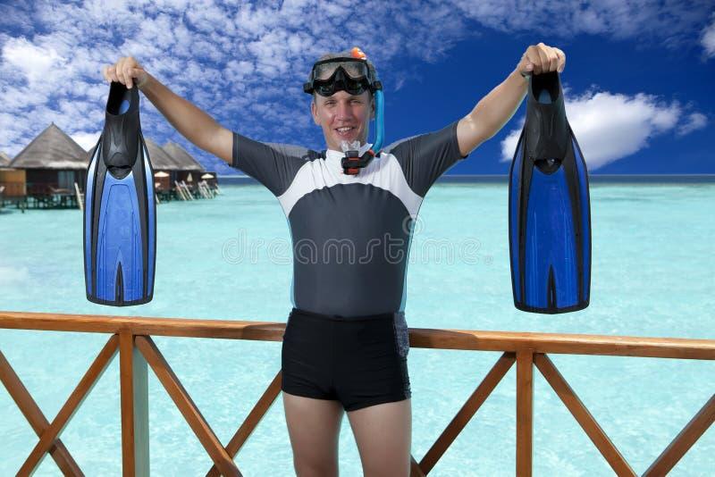 Jeune homme de sports avec les nageoires, le masque et le tube près de la mer maldives photos stock