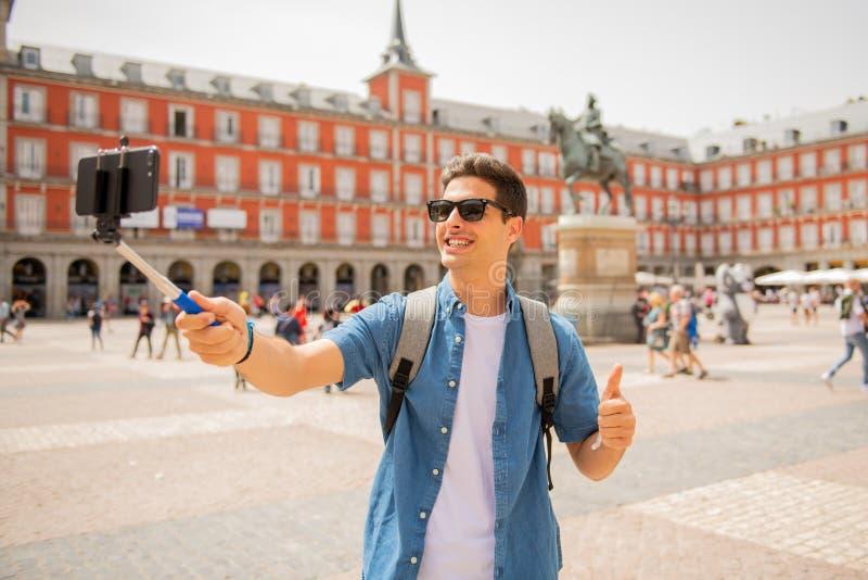 Jeune homme de touristes caucasien beau heureux et enthousiaste prenant un selfie dans maire de plaza, Madrid Espagne photo stock