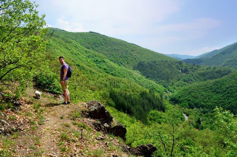 Jeune homme de touristes voyageant dans la montagne verte d'été photo stock