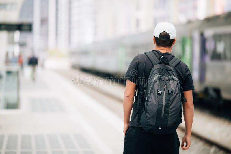 Jeune homme de voyageur avec le sac à dos dans le chemin de fer à la station de train concept de course images stock